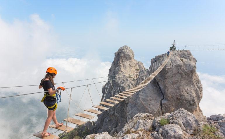 Woman Crossing Mountain Bridge